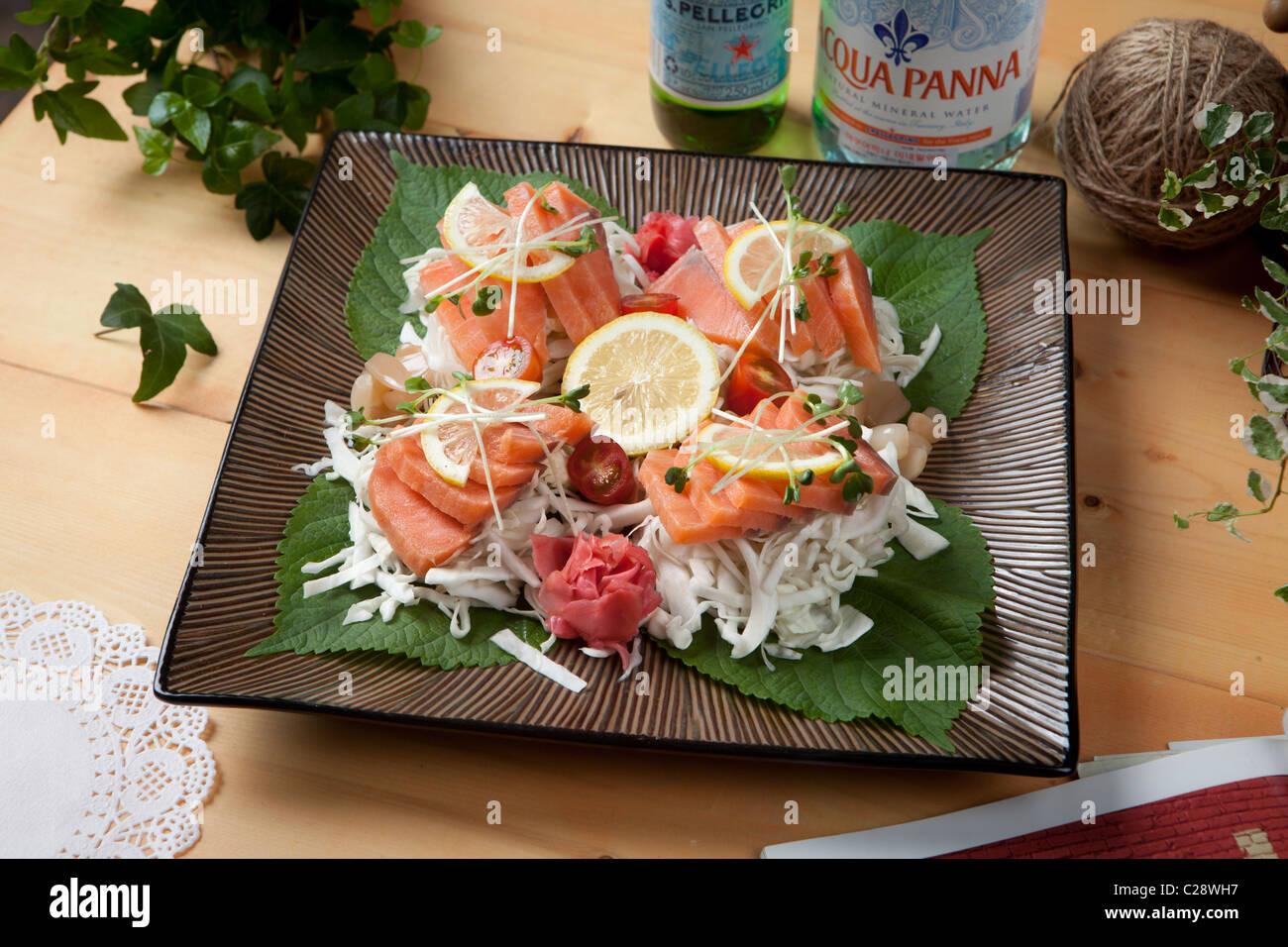 Korean food sale on restaurant , South Korea Salmon sashimi (Raw fish) with lemon and garlic - Stock Image