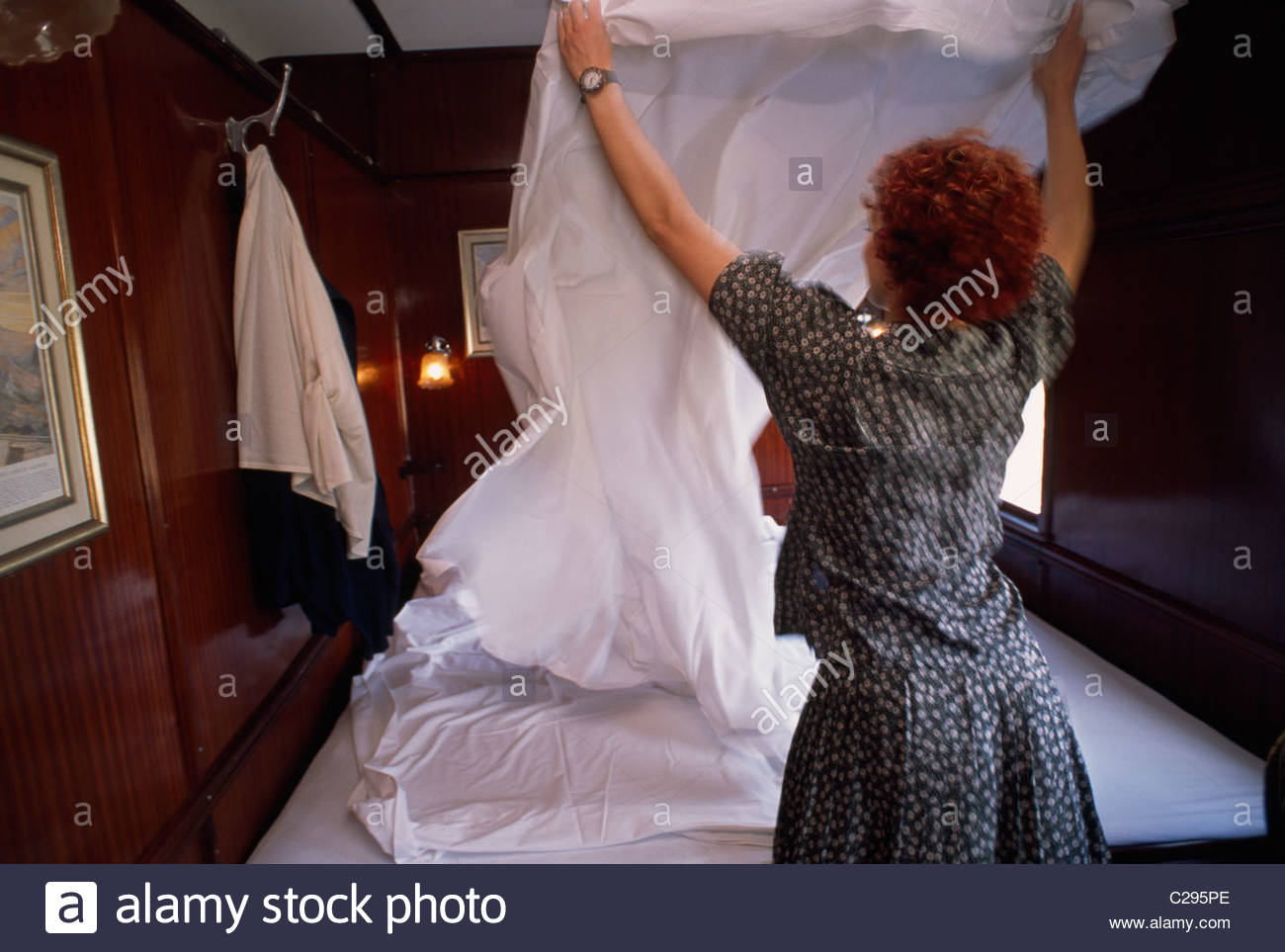 Attendant making up a double bed in a train suite. - Stock Image