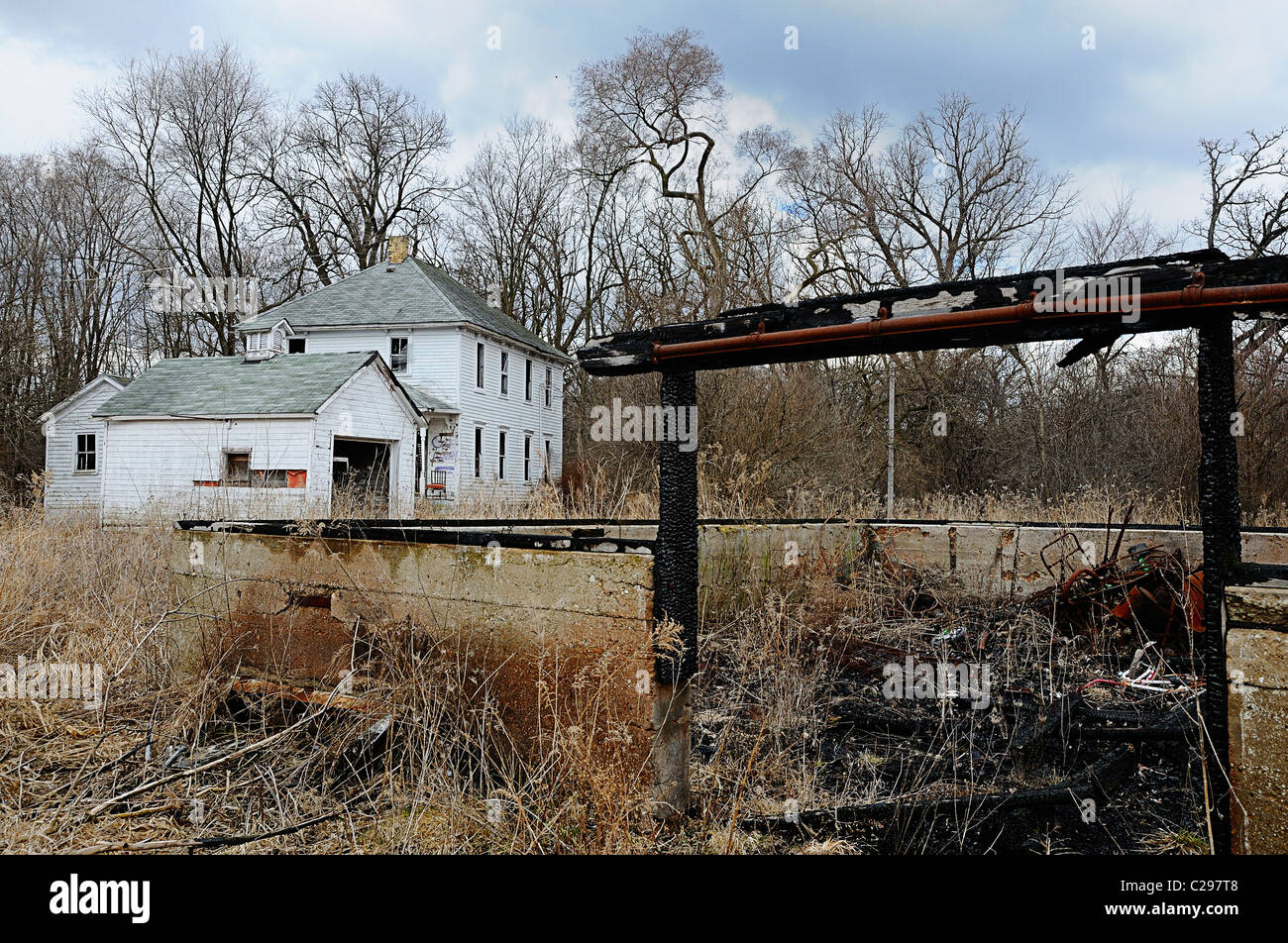 Burned remains of farm building and run down house. - Stock Image