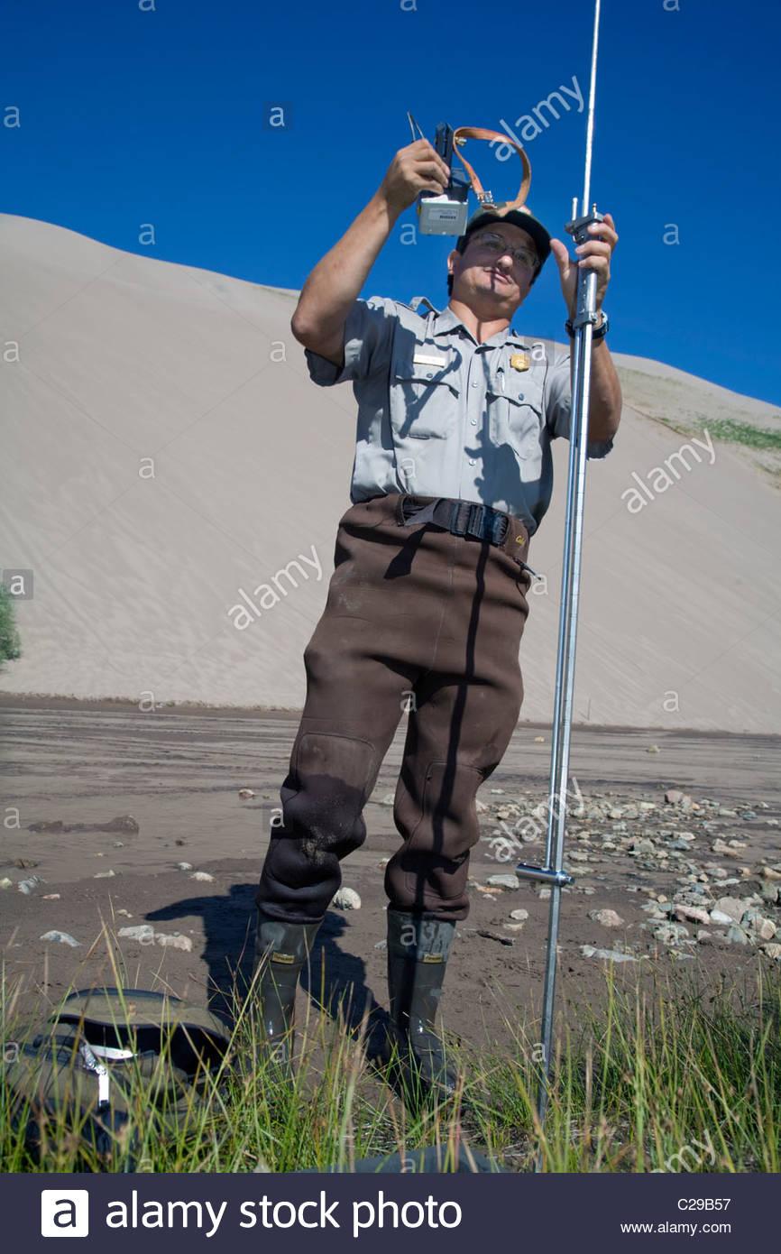 A park geologist measures water flow in Medano Creek. - Stock Image