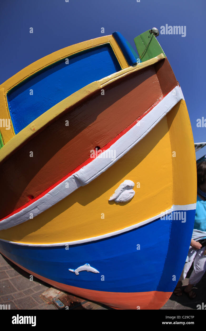 small  maltese malta fishing boat beached painted in bright colors - Stock Image