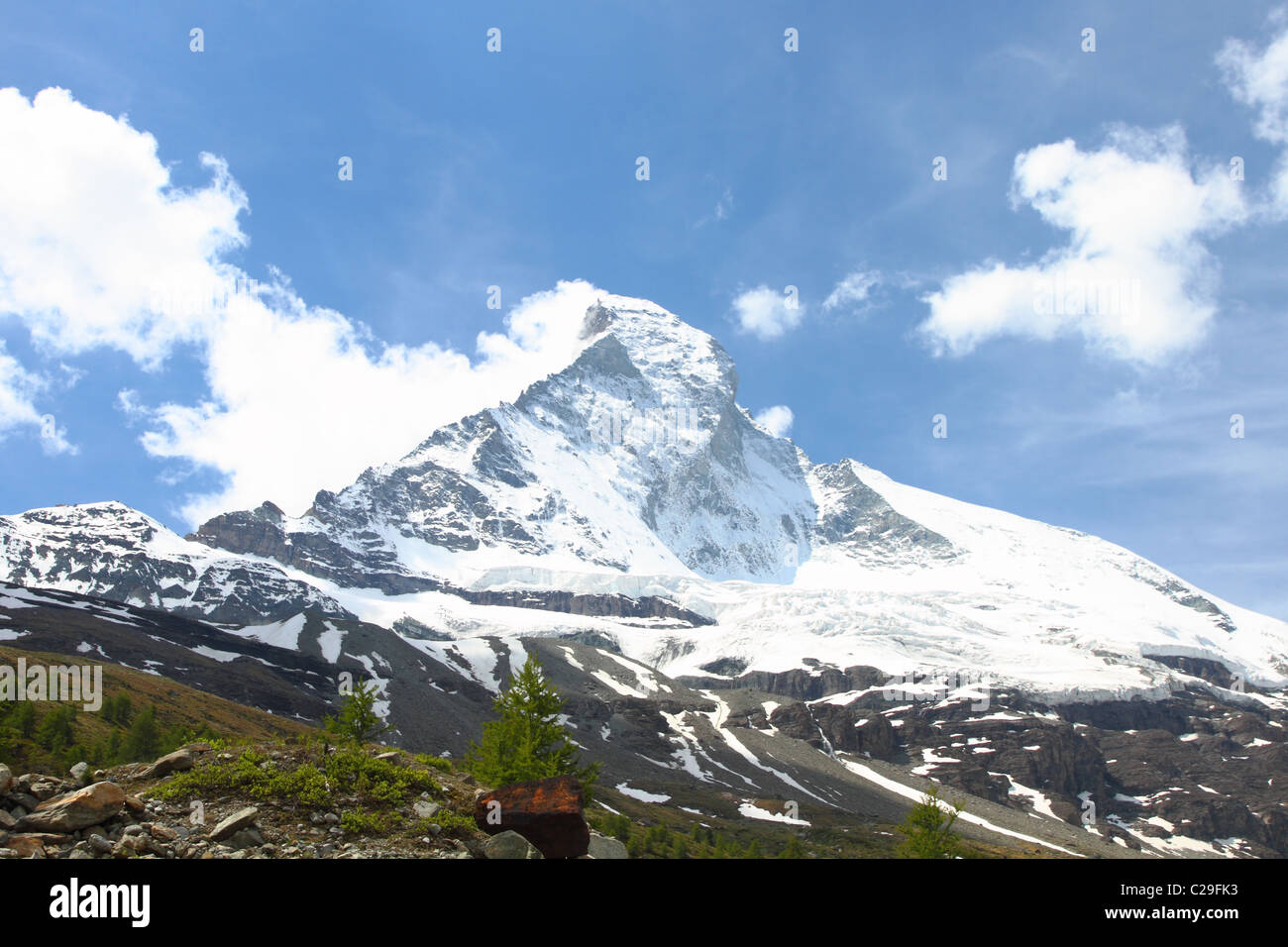 famous swiss iconic mountain Matterhorn rising snow covered from bare grounds seen from an unusual angle - Stock Image