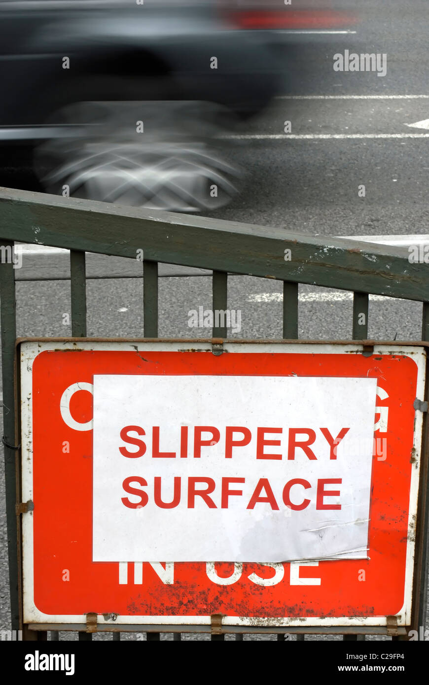 slippery surface sign beside a road in richmond upon thames, surrey, england - Stock Image
