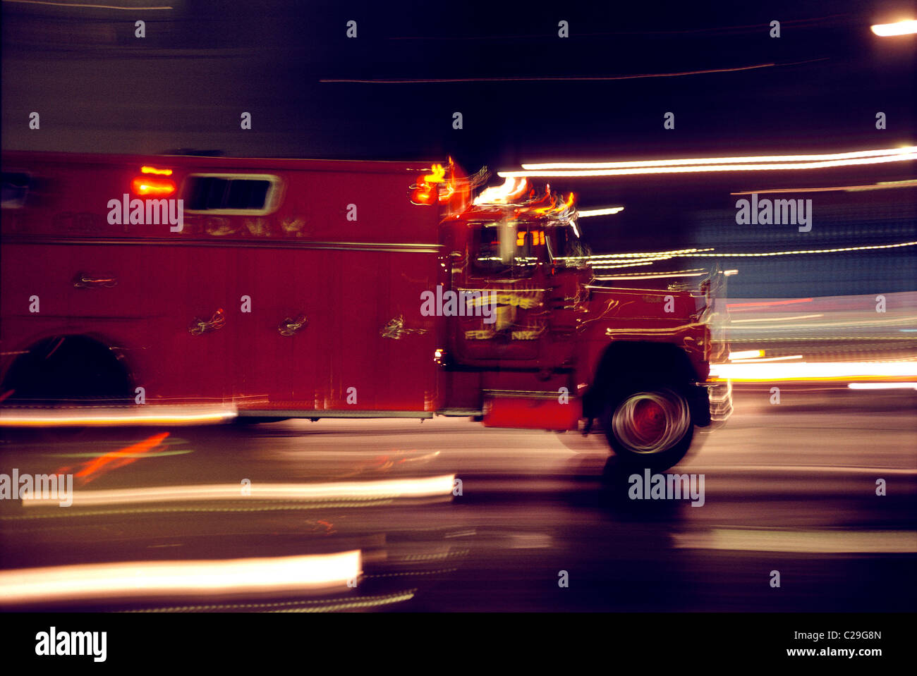 Blurred motion view of a fire truck racing to an emergency at night Stock Photo
