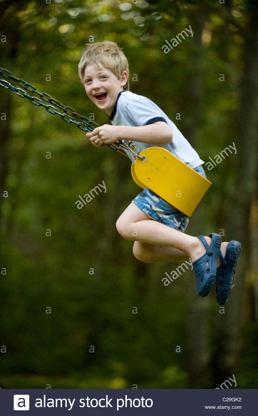 A young boy swings on a swing set. - Stock Image