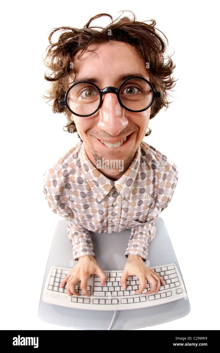 Fish-eye shot of a smiling tousled nerd typing on the keyboard - Stock Image