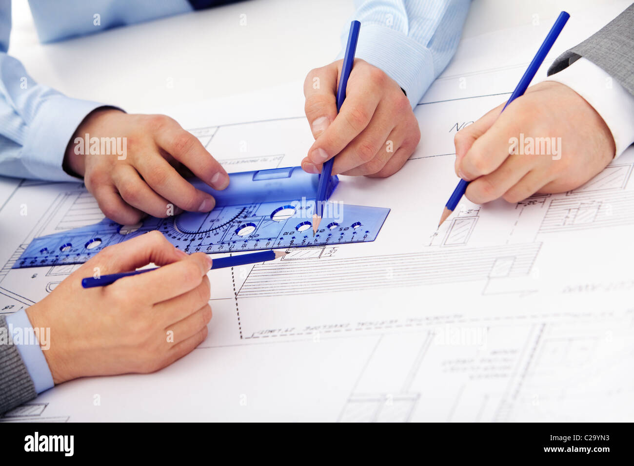 Three pairs of hands sketching a housing project Stock Photo
