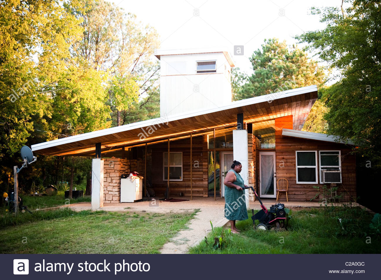 A woman cuts grass in her front yard in rural Alabama. - Stock Image