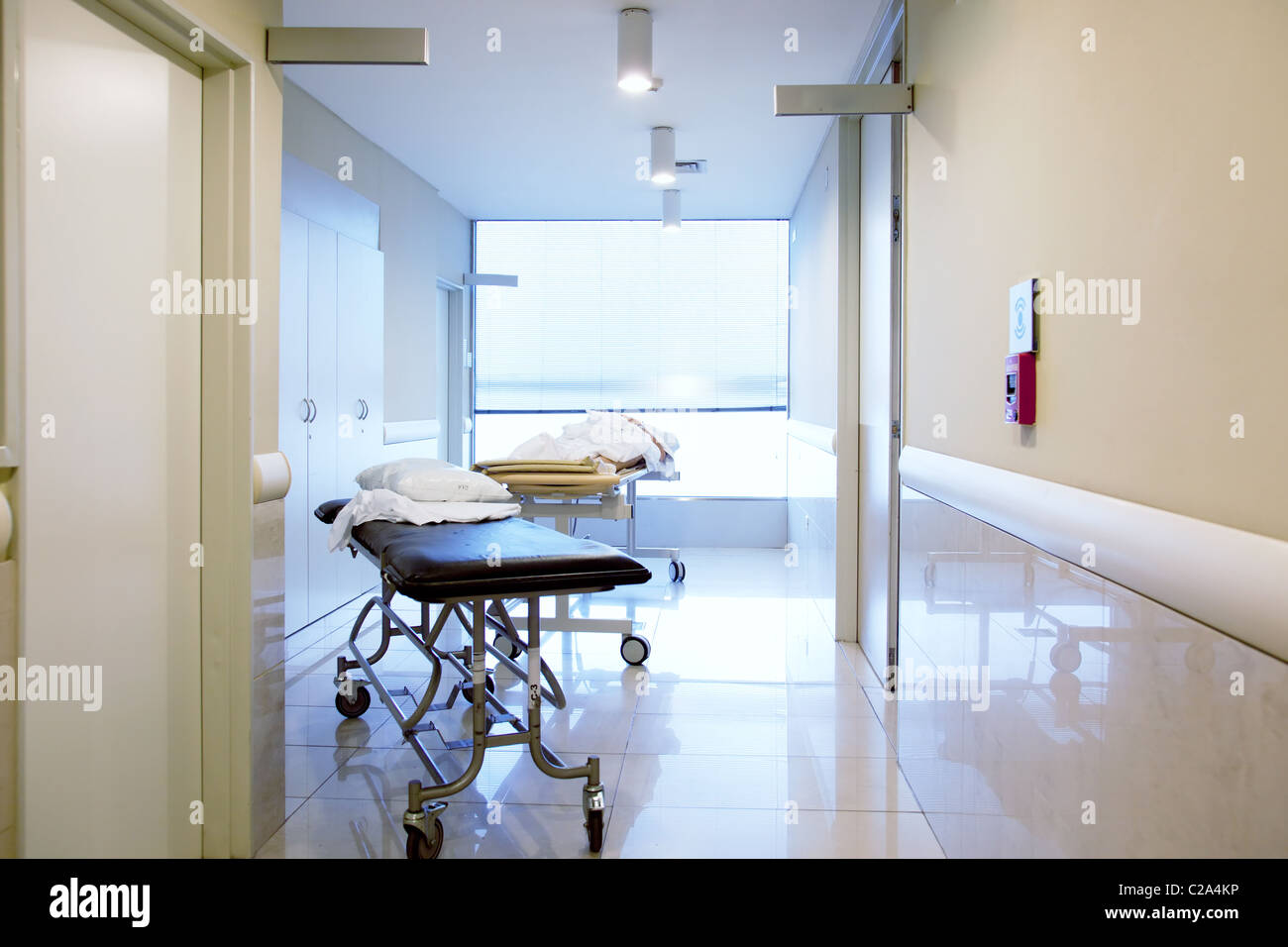 An interior of a hospital hallway with a couple stretchers - Stock Image