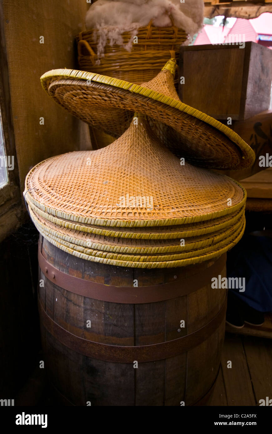 Wide-brimmed woven wicker sun hats on sale for Chinese gold miners. - Stock Image