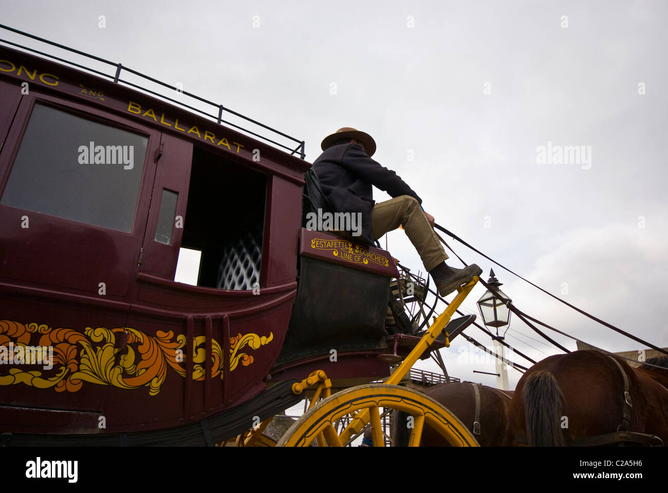A coachman drives a stagecoach and team of horses. - Stock Image