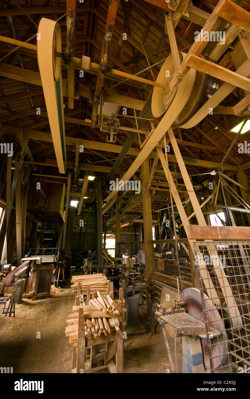 Large belts spin on pulleys on a wheelwright's plant sizing machine. - Stock Image