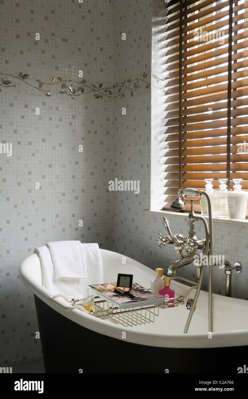 Freestanding bath under closed blinds with wall motif tiling - Stock Image