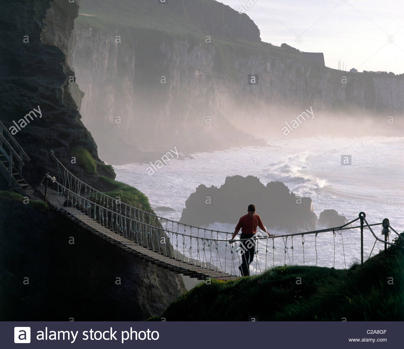 Crossing Carrick-a-rede rope bridge on the north Antrim coast. - Stock Image
