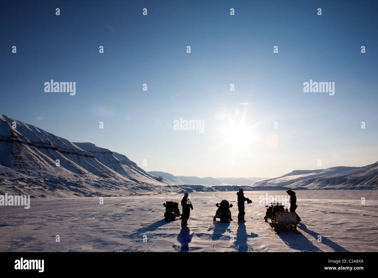 Three people on a winter snowmobile adventure in Svalbard, Norway - Stock Image