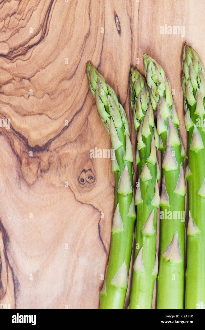 Asparagus Spears on a olive wood board - Stock Image
