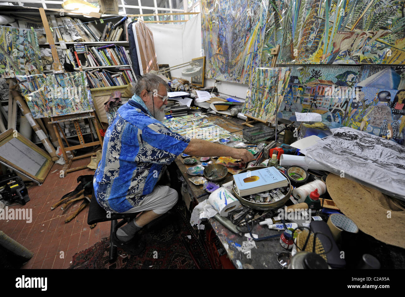 Painter Michael Adams sitting in his studio at Anse Poules Bleues, Mahé Island, Seychelles - Stock Image