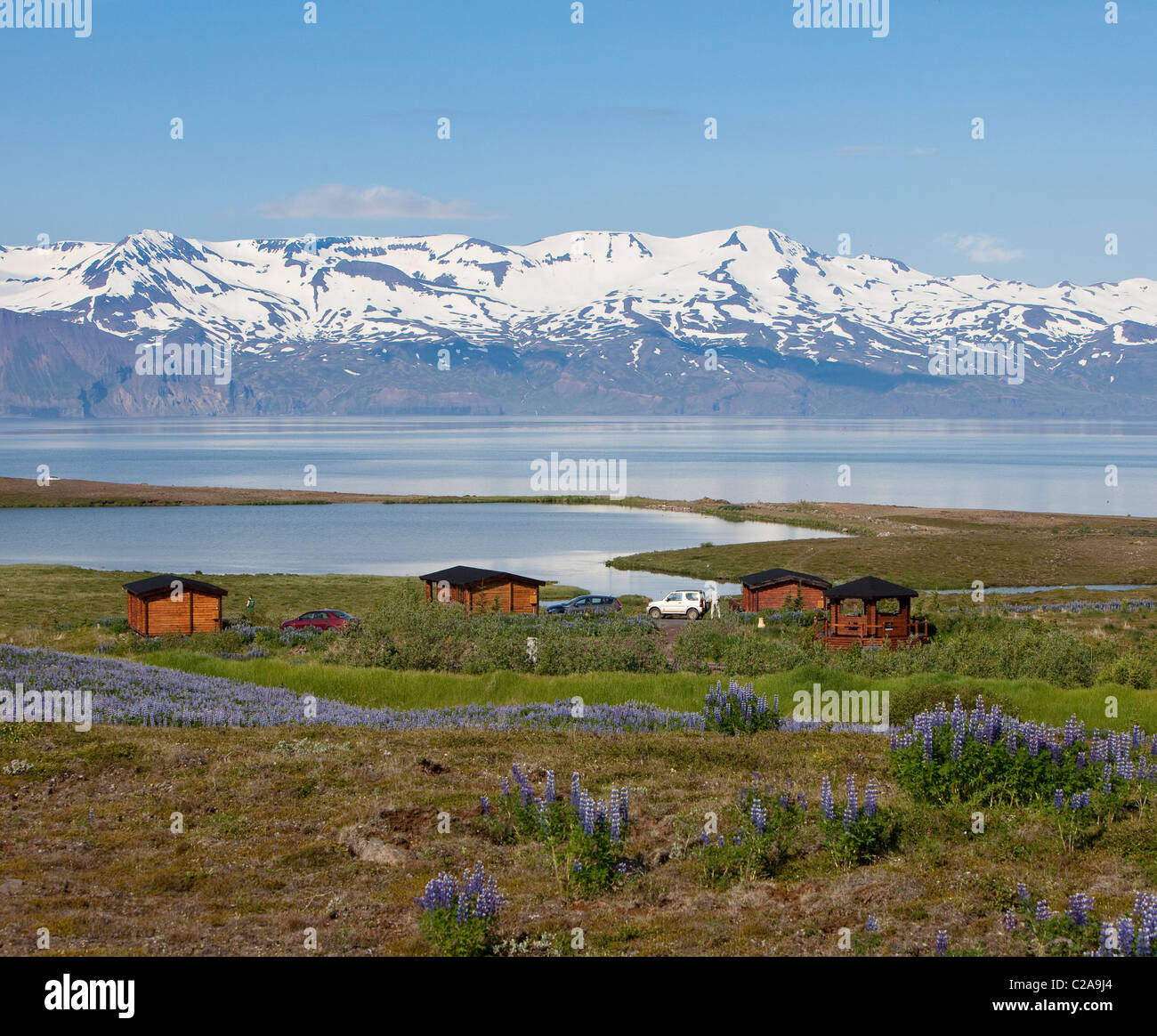 Summer house overlooking water and mountains, Skjalfandi bay, Tjornes Peninsula, Iceland - Stock Image
