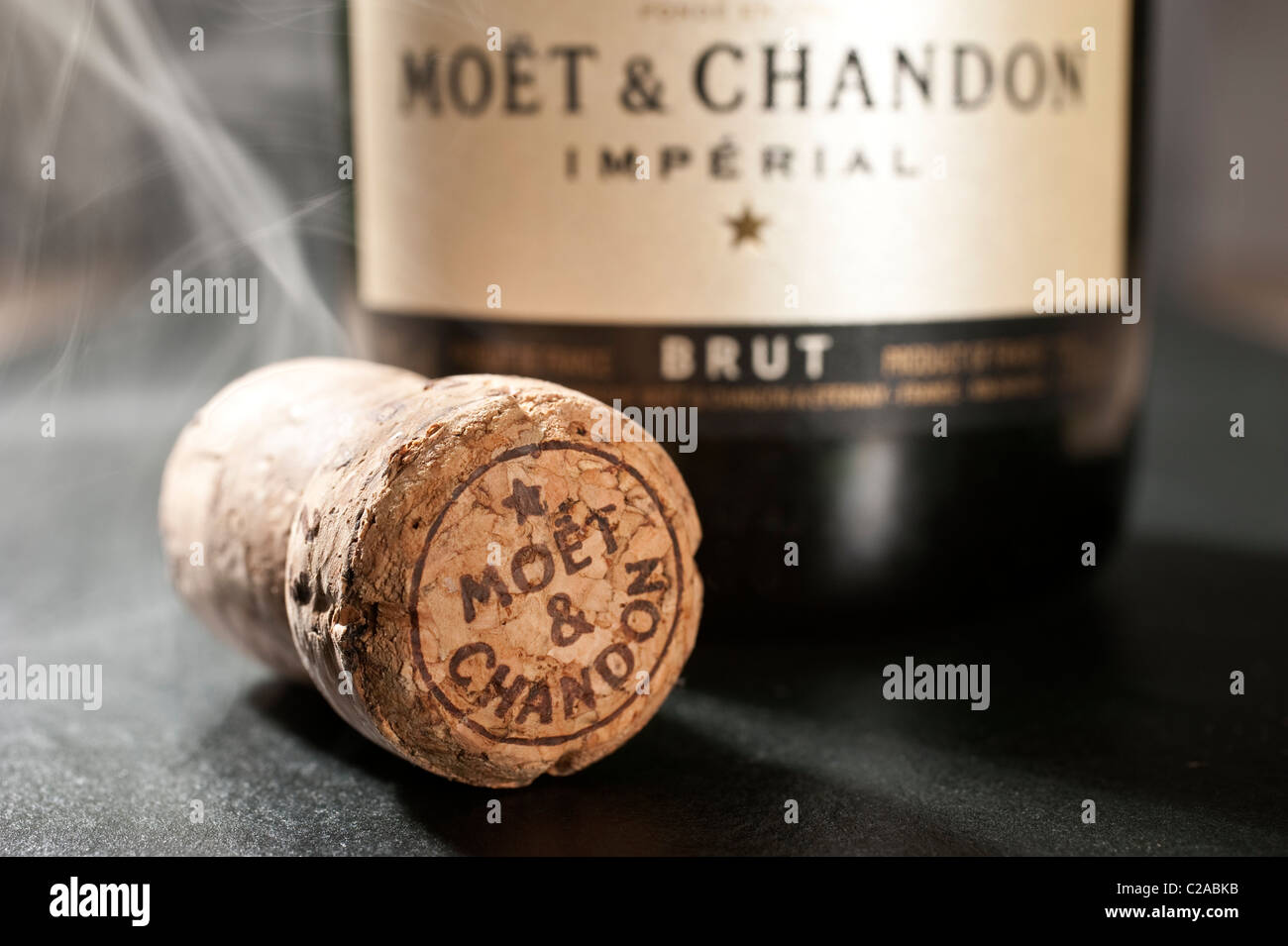 The cork and bottle of Moet and Chandon Champagne, wreathed in cigar or cigarette smoke - Stock Image