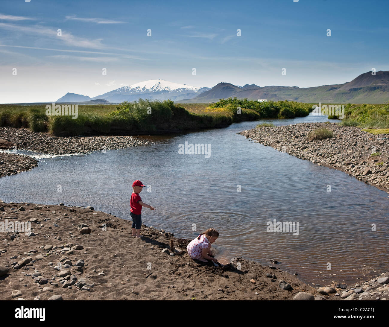 Brother and sister exploring rocky beach, Snaefellsjokull glacier in background, Snaefellsnes Peninsula, Iceland - Stock Image
