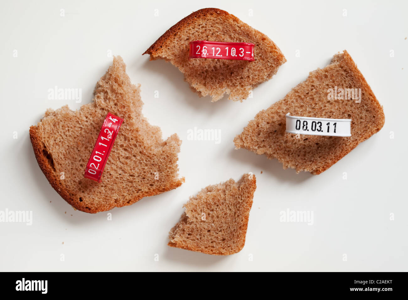 Four pieces of bread slice and seals with printed production date - Stock Image