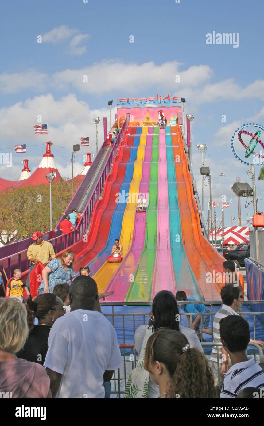 Ethnic kids down giant slide at Miami Dade County Fair Miami Florida - Stock Image