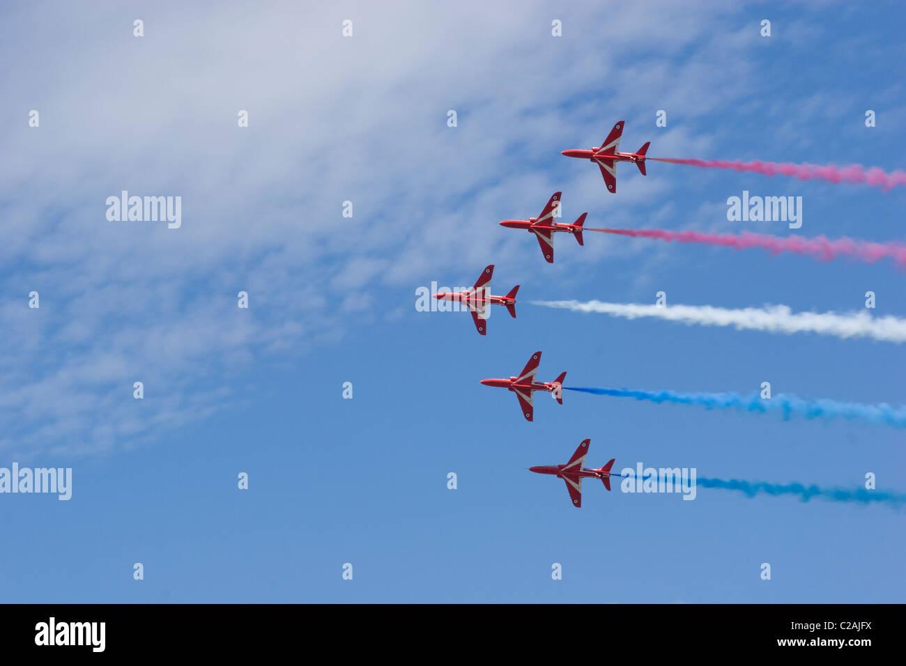 Red Arrows formation flying V aerobatics smoke trail Hawk white blue vapour blue sky sun underside 5 five close - Stock Image