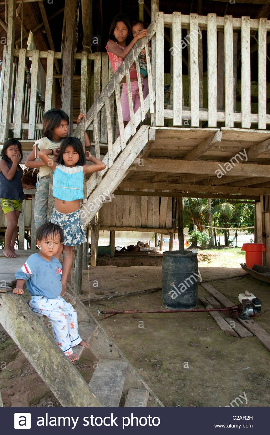 Peruvian children stand staggered on the stairs of a local hut. - Stock Image