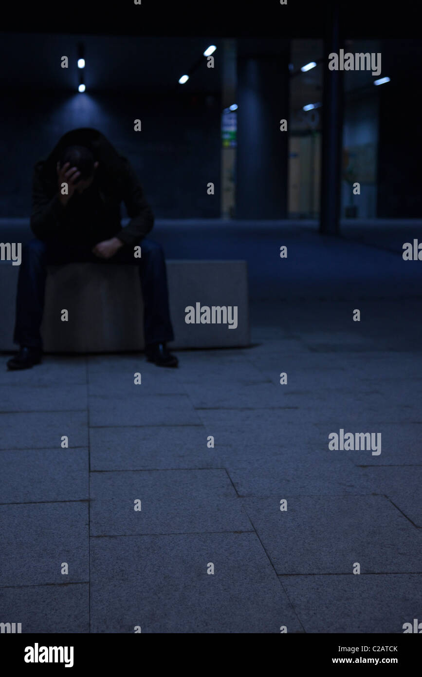 Man sitting outside at night with head in hands - Stock Image