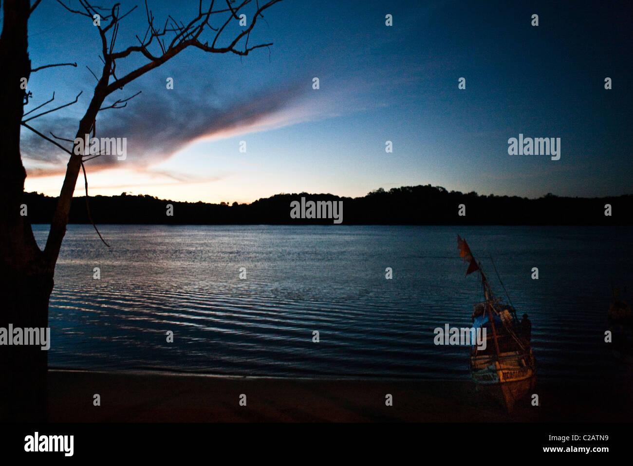 South America, Amazon, fishing boat coming into shore at dusk - Stock Image