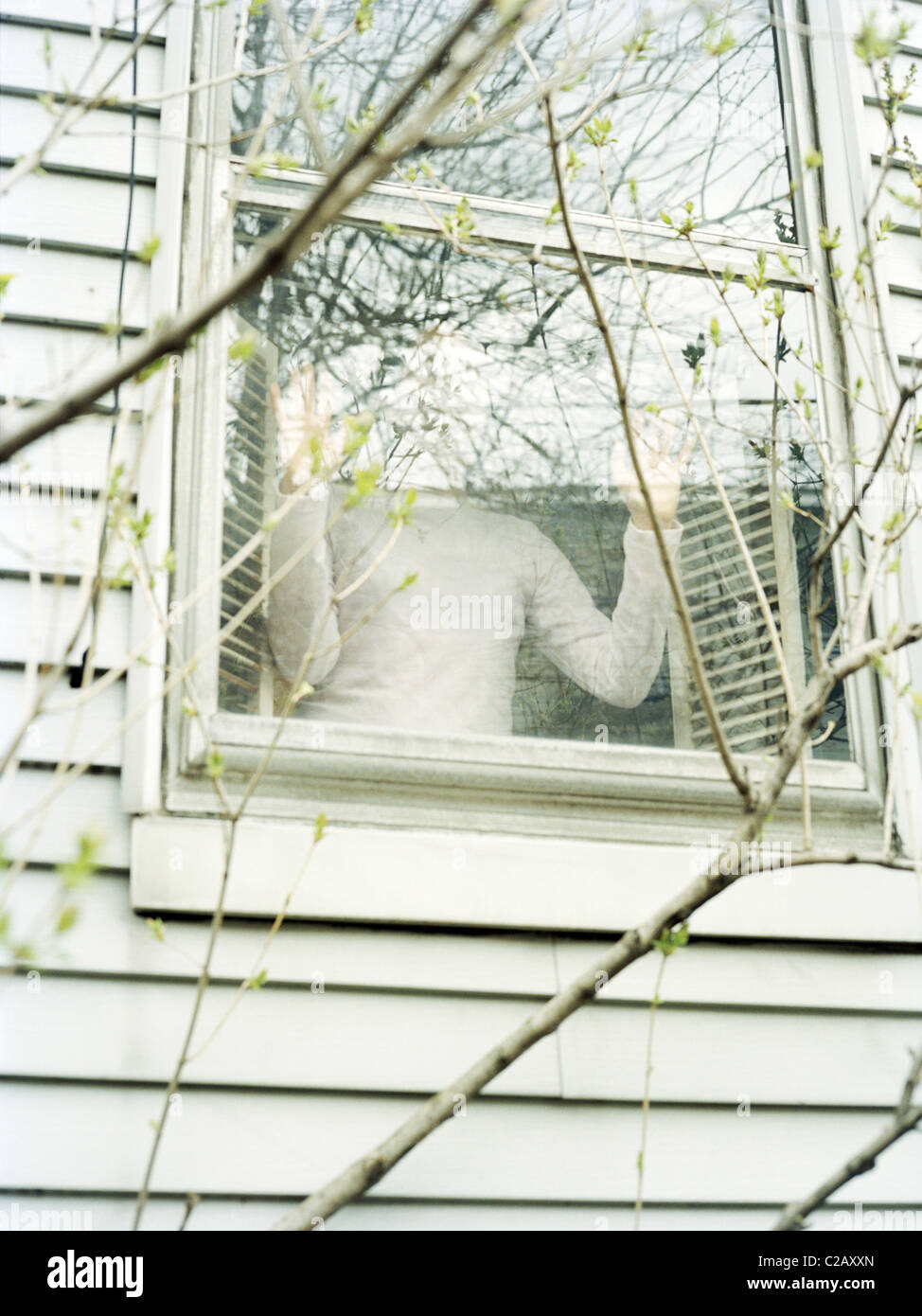 Person looking out window - Stock Image