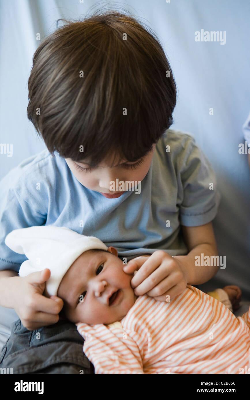 Young boy touching baby sibling's cheek - Stock Image