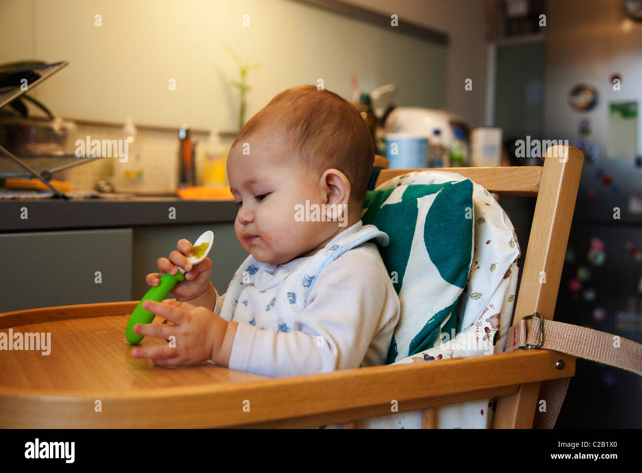 Baby girl eating, playing with spoon - Stock Image