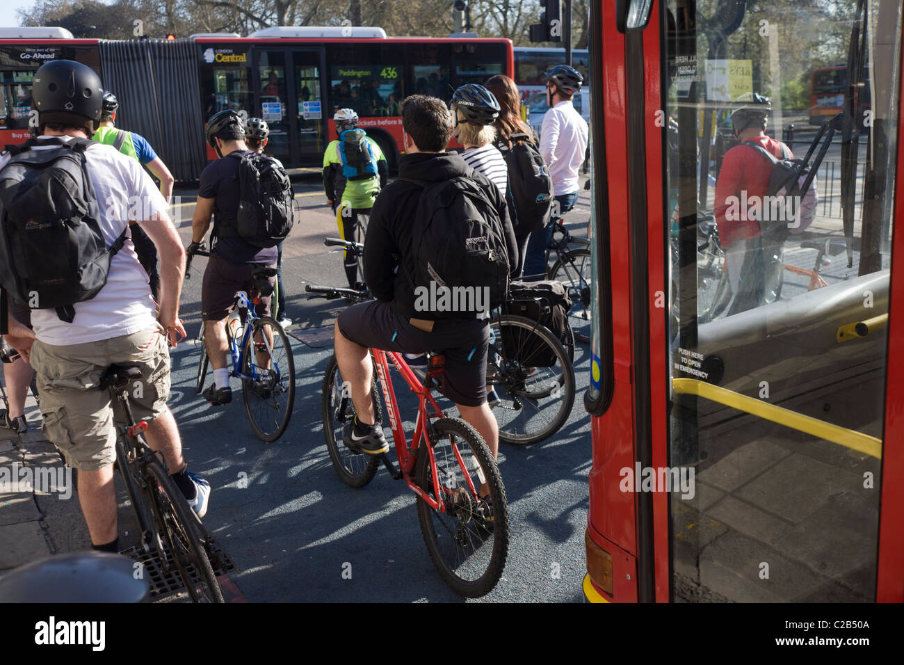 Group of cycling commuters stopped at traffic lights at Kennington, south London. - Stock Image