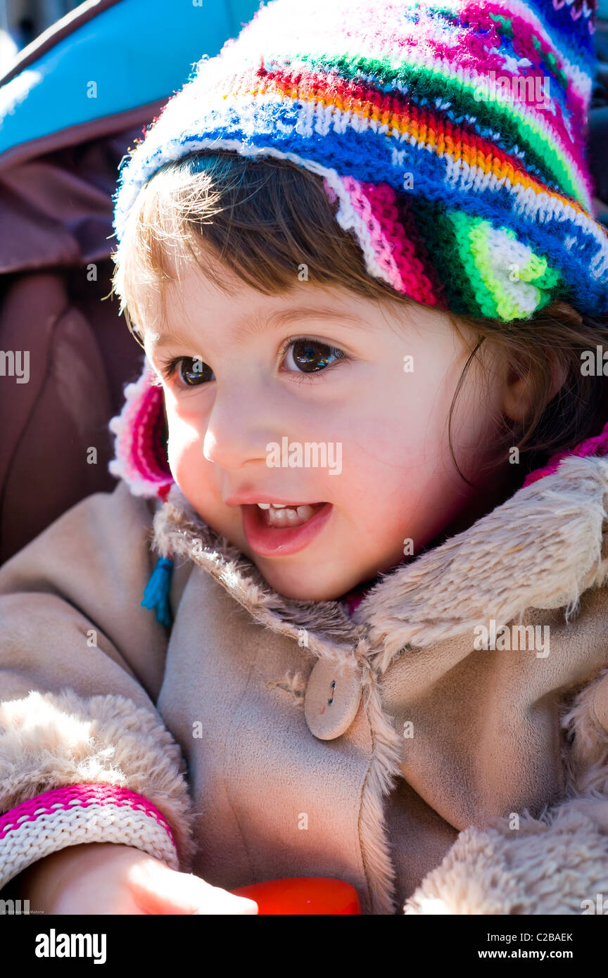 Baby girl smiling wearing winter outfit - Stock Image