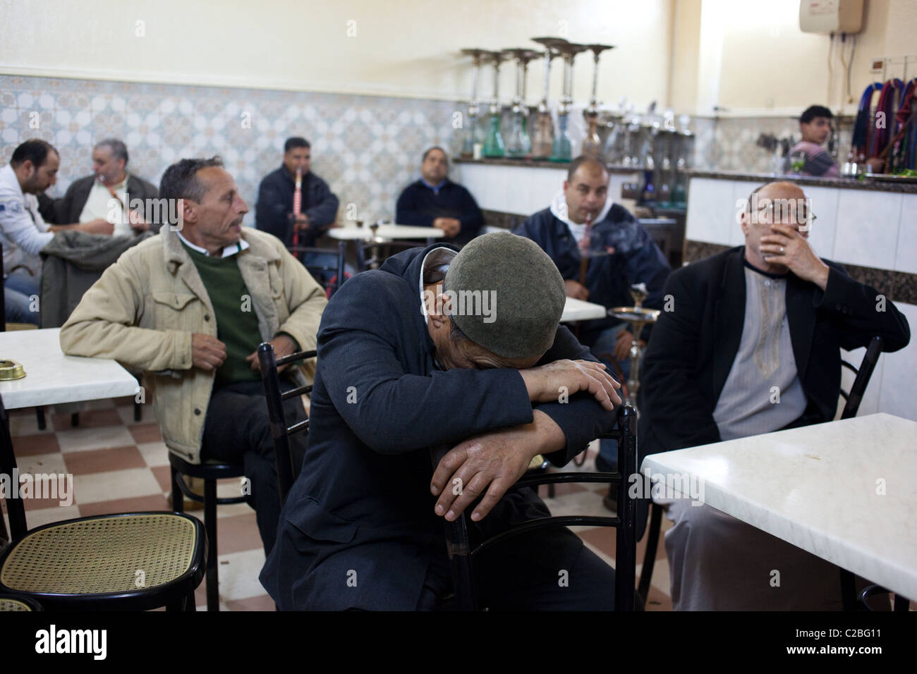 Men smoke cigarettes and shisha and drink coffee in a traditional coffeehouse in Sousse, Tunisia. Stock Photo