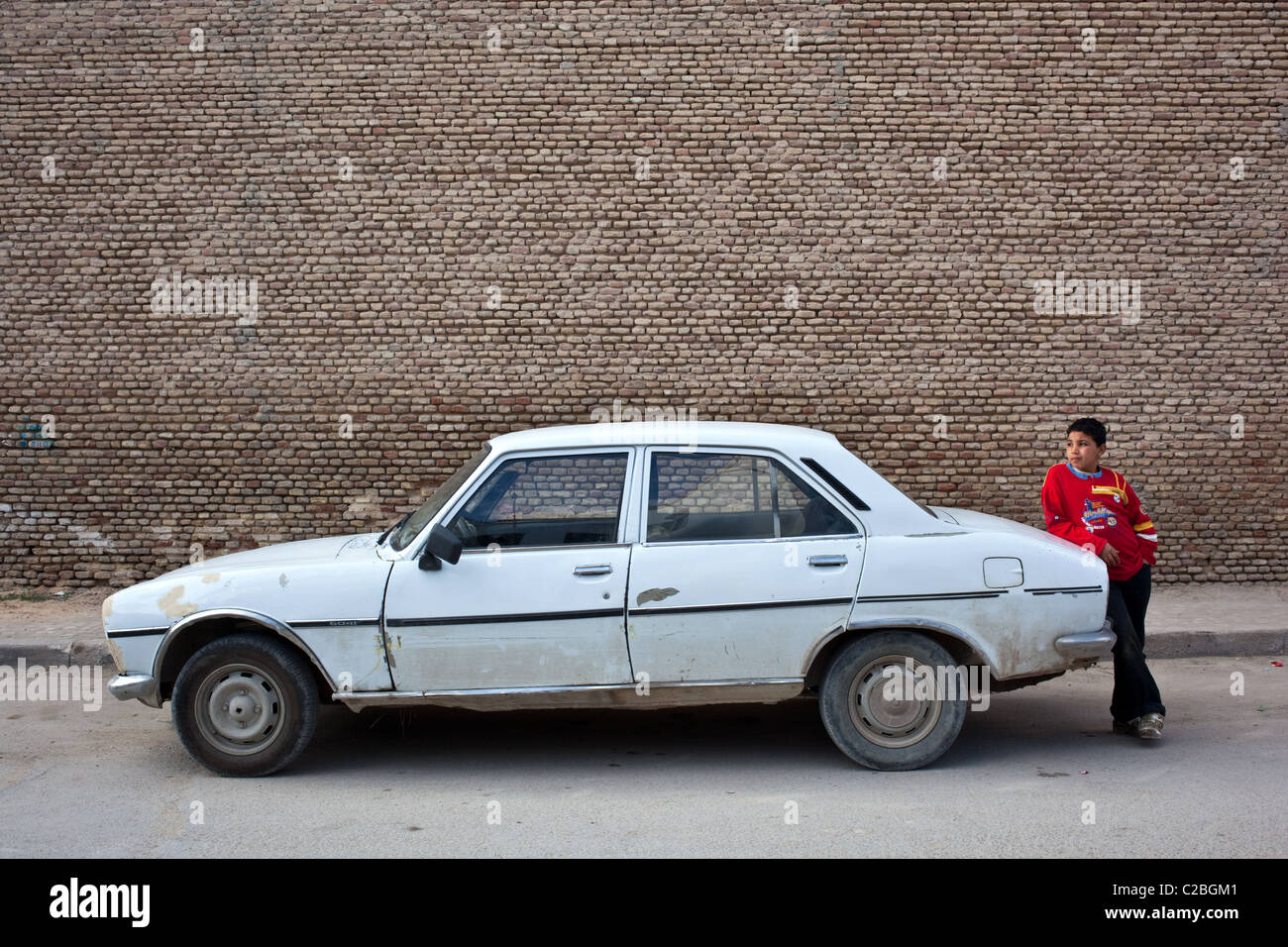 A Young Boy Stands By An Old Peugeot 504 Car In The Old City Of