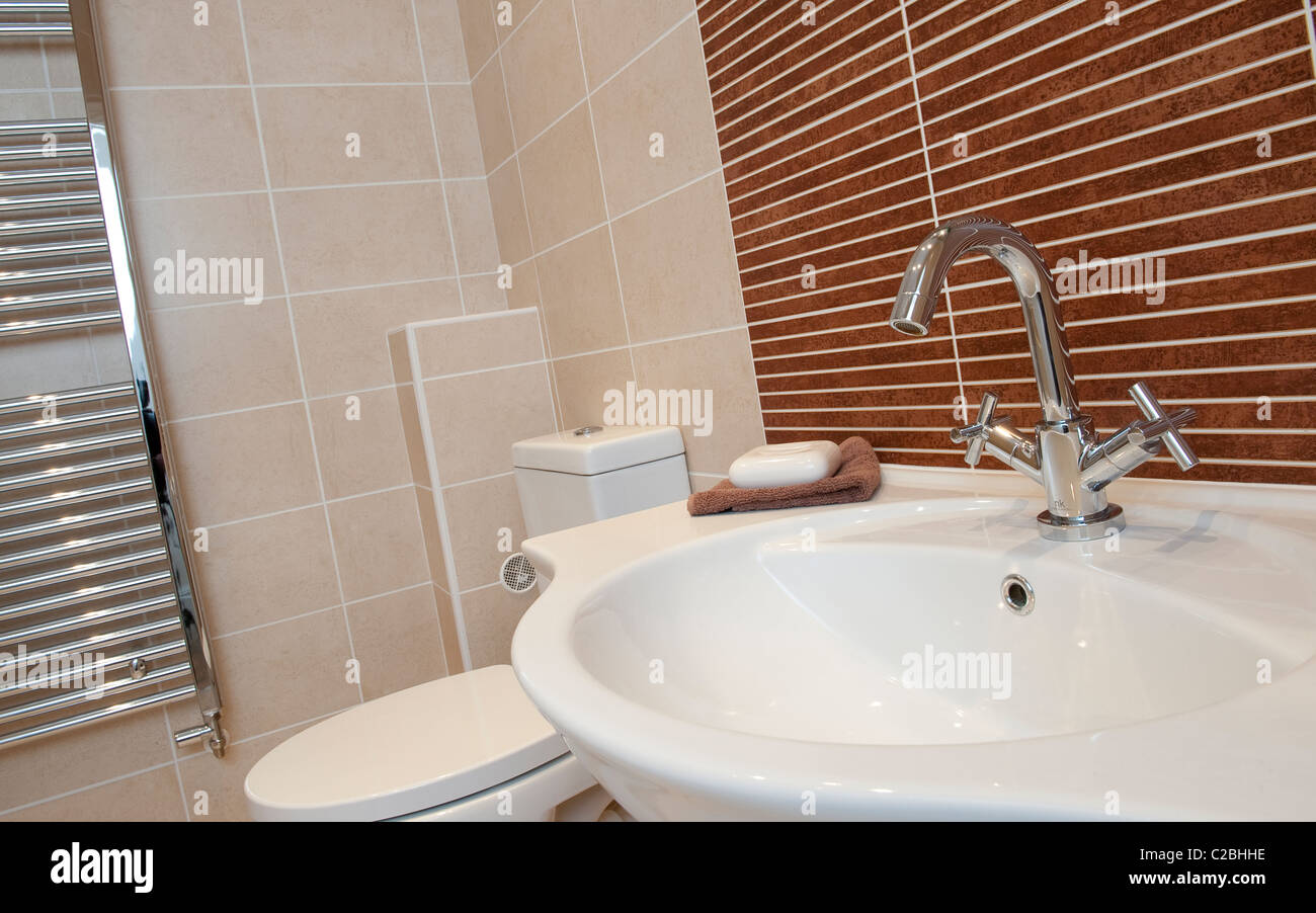 Hand basin and toilet in a modern bathroom. - Stock Image