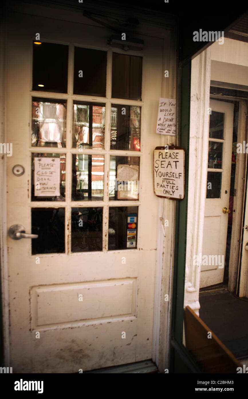 Entrance to a restaurant in the West Village manhattan New York with various quirky signs stuck & Manhattan Door Entrance Signs Stock Photos \u0026 Manhattan Door Entrance ...