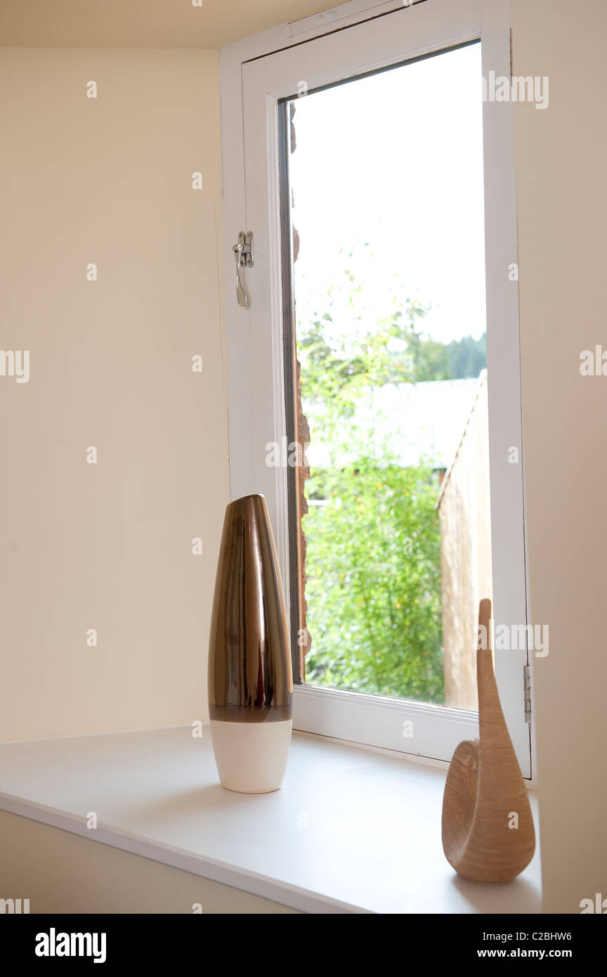Modern vase and ornament on the windowsill of a house. - Stock Image