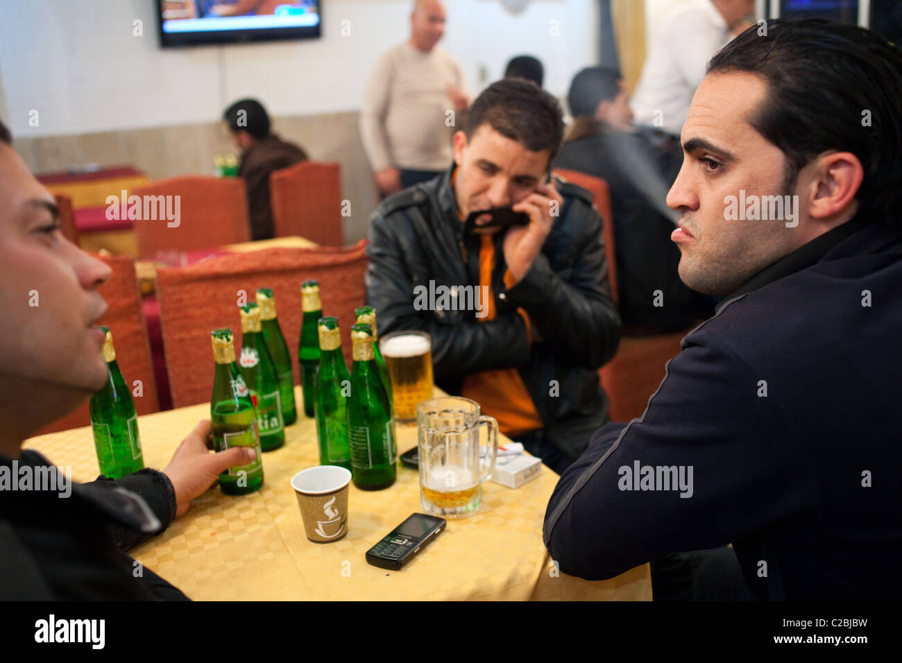 Young customers drink  beer, coffee and smoke cigarettes in a hotel bar serving alcohol in Sfax, Tunisia. - Stock Image