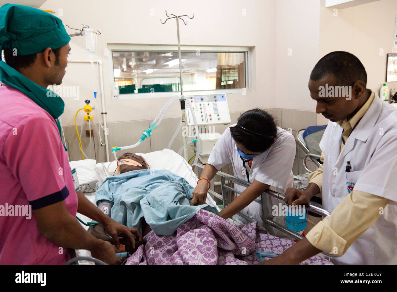 Medical staff treat a patient in an Intensive Care Unit (ICU) at Yashodhara Hospital Sholapur India - Stock Image