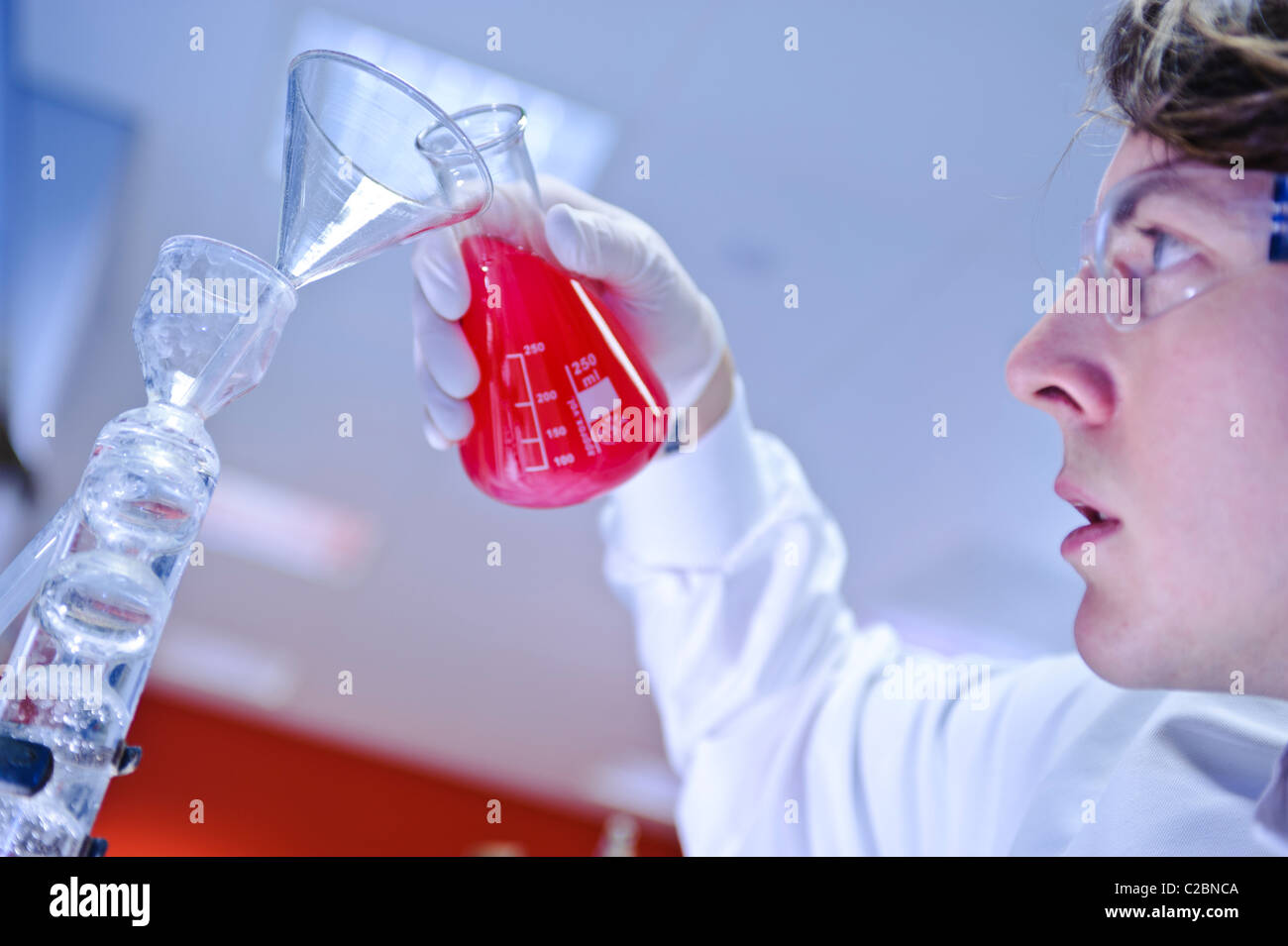 Young make scientist wearing goggles gloves and lab coat pouring bright red liquid from glass beaker into in science - Stock Image
