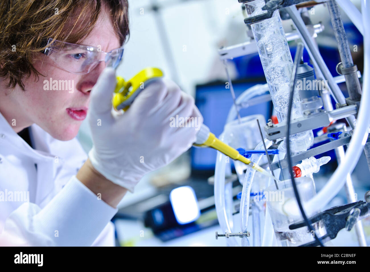 Young male scientist wearing goggles and white lab coat pipetting into scientific apparatus in science lab - Stock Image