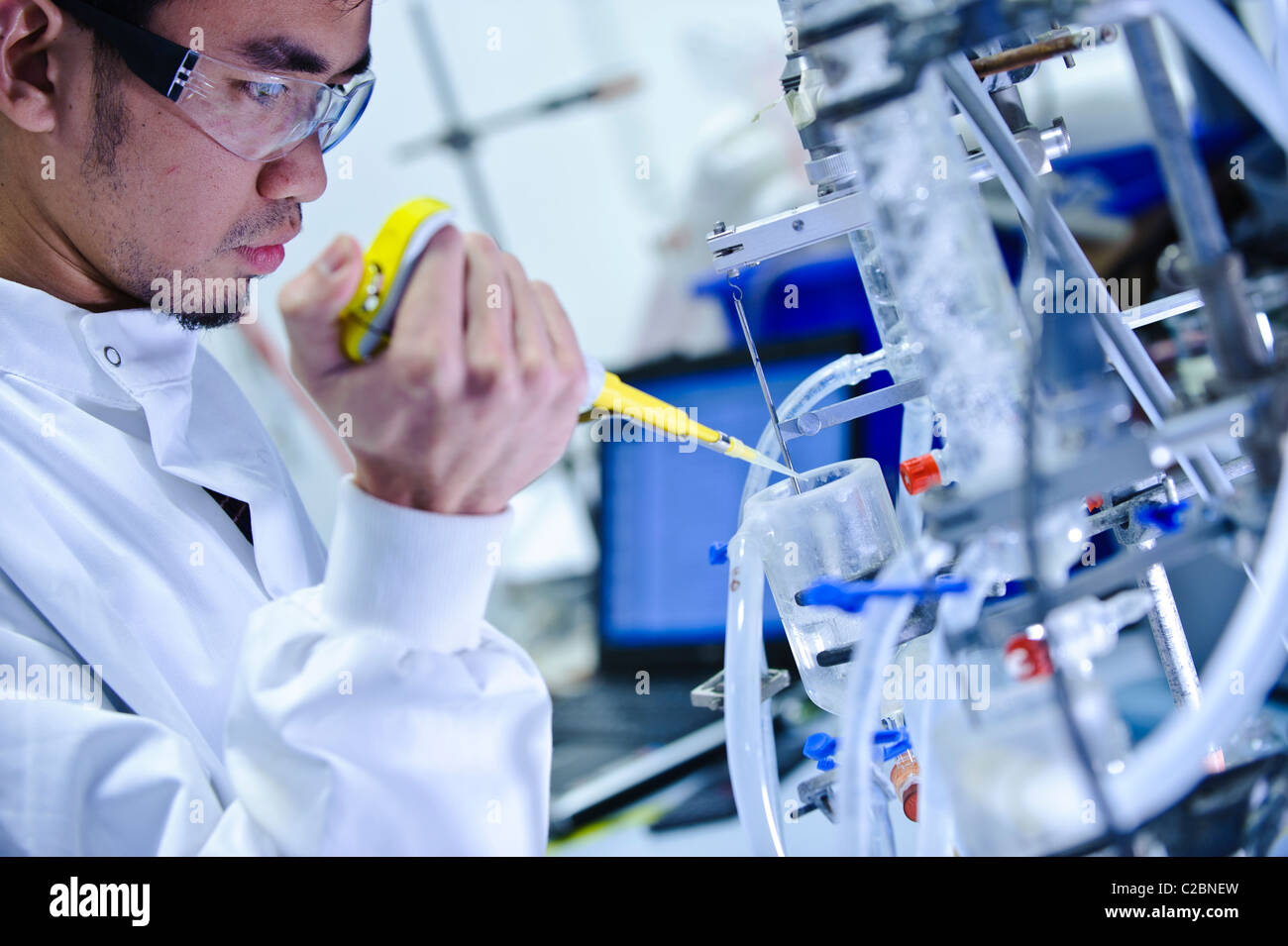 Young Asian male scientist wearing clear goggles and white science coat looking at glass tube apparatus in science - Stock Image
