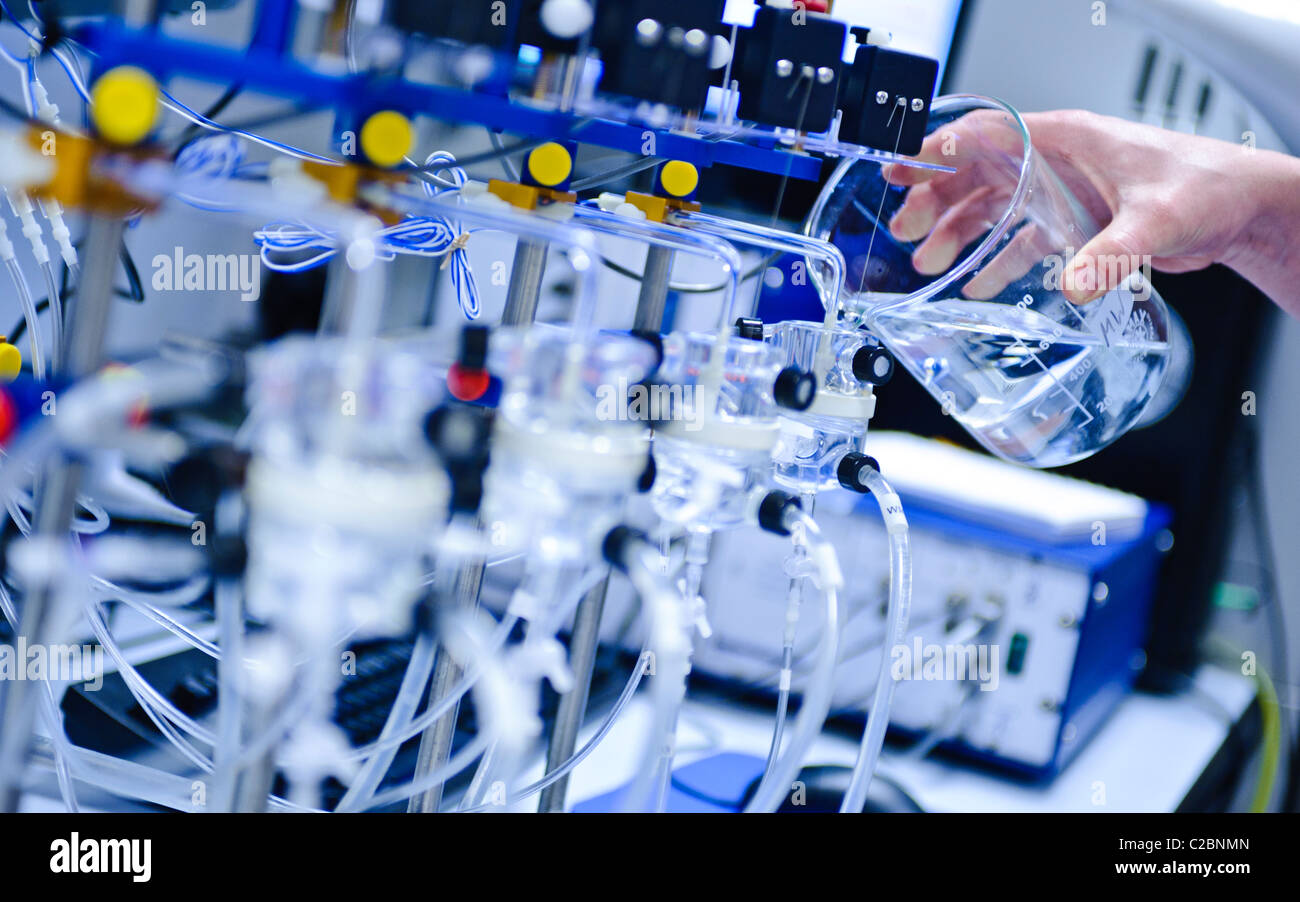Glass beaker pouring clear solution into scientific apparatus in a science lab - Stock Image