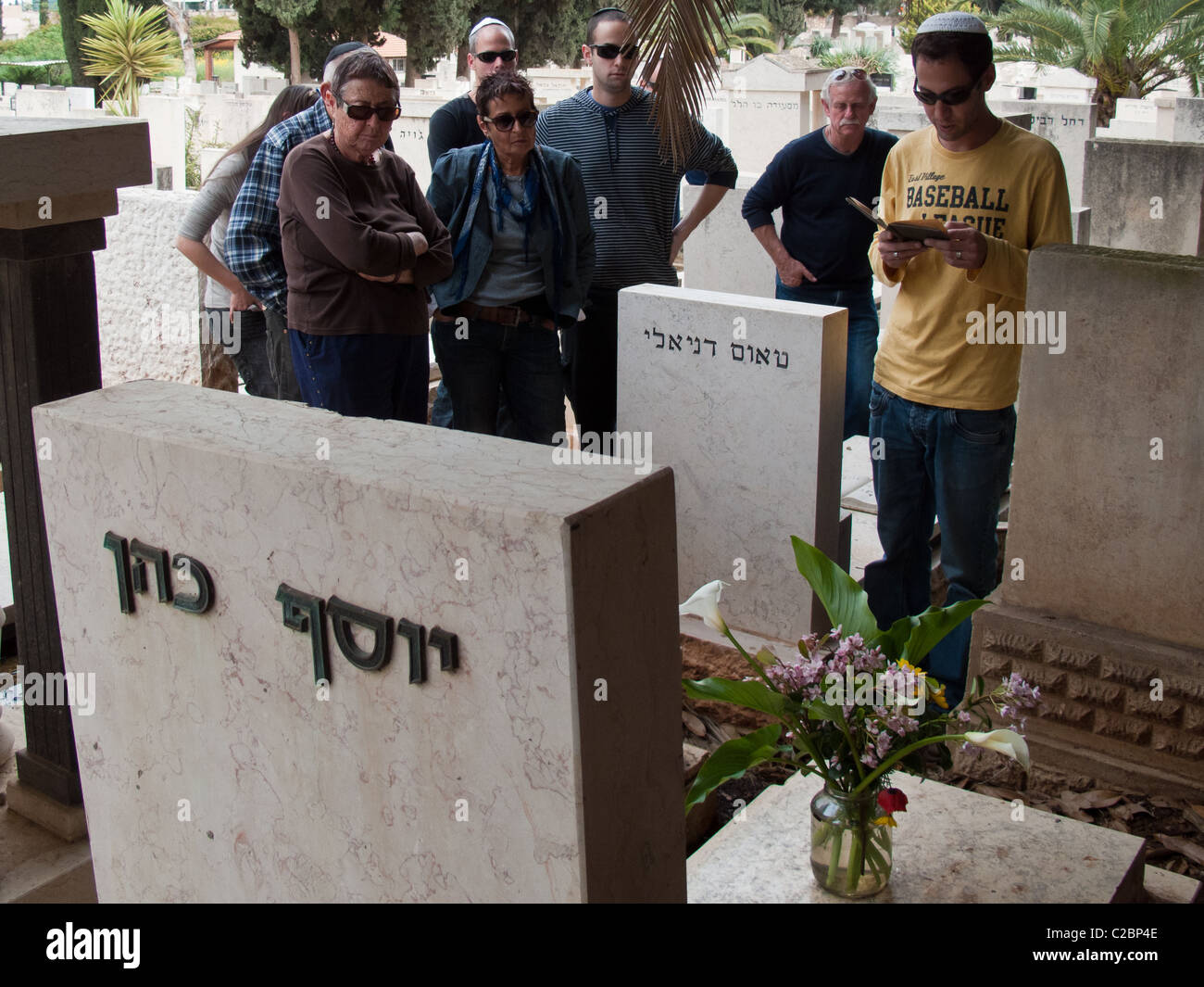 Secular Jewish family conducting a memorial service in cemetery - Stock Image