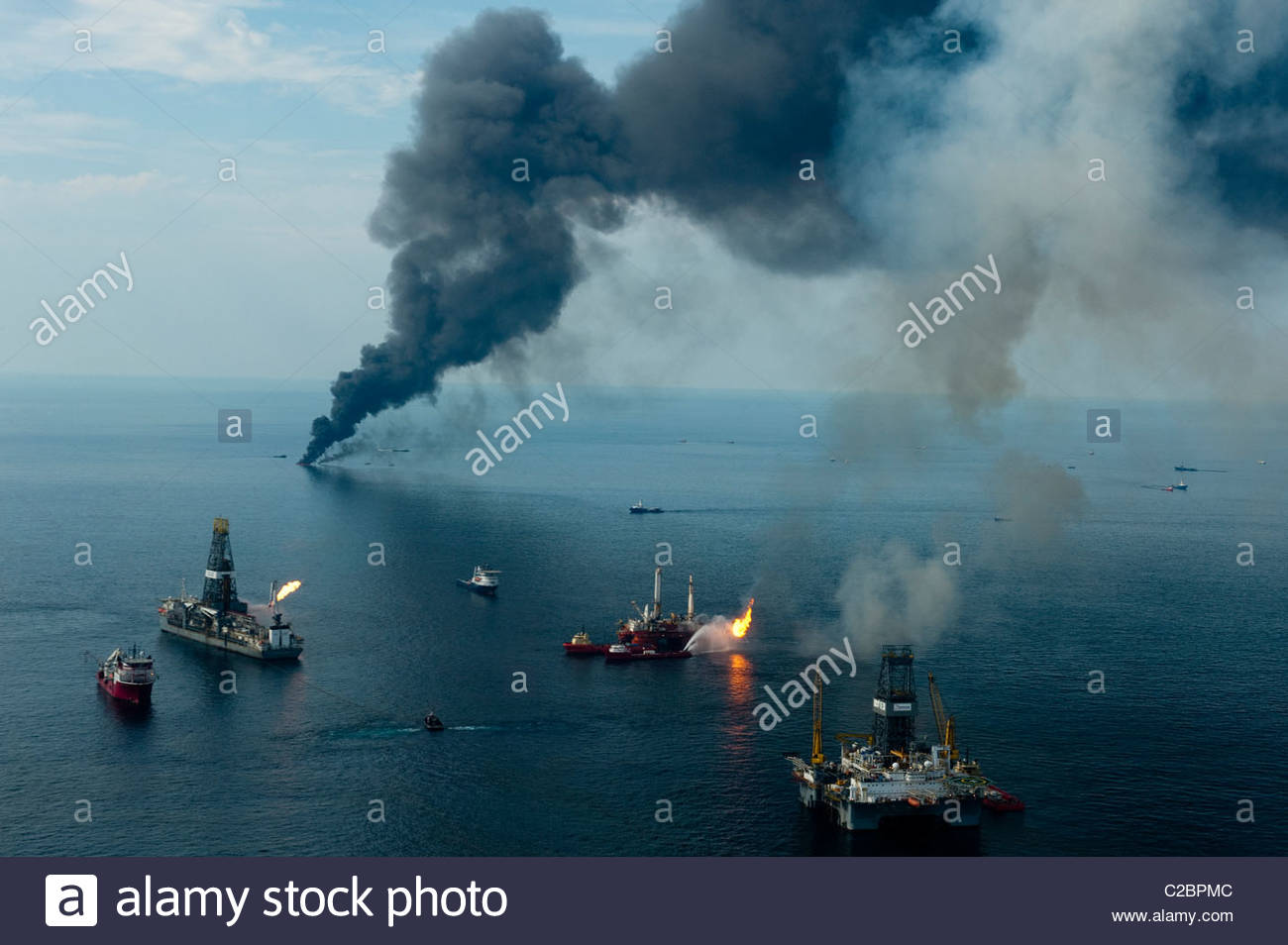 Smoke rises from surface oil being burned by cleanup crews. - Stock Image