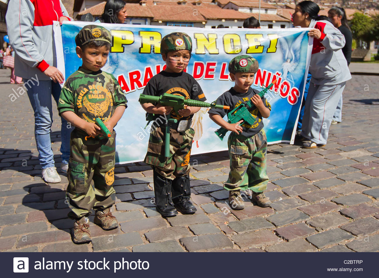 Boys dressed in military uniforms at the Pronoei holiday parade. - Stock Image