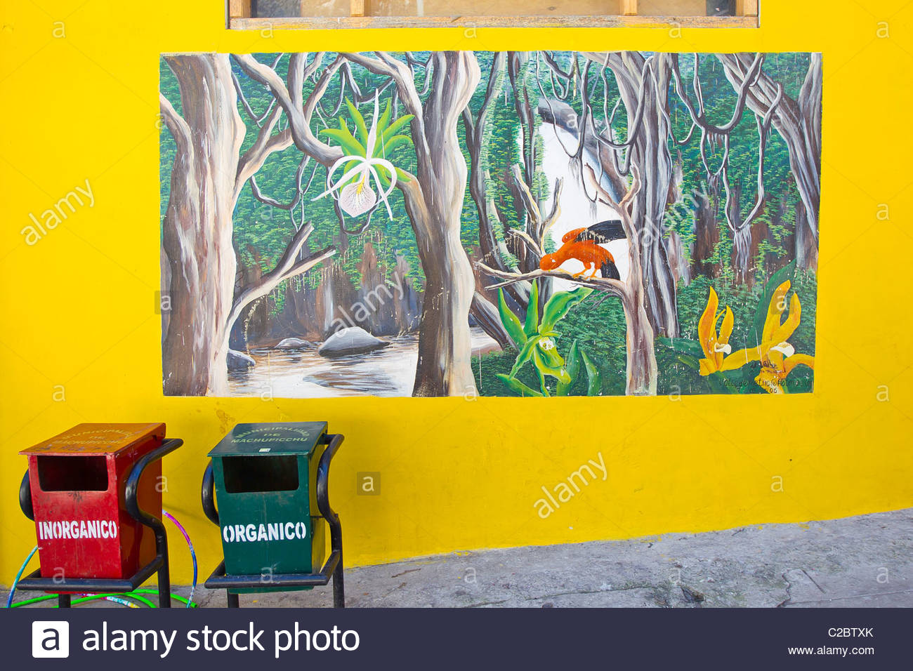 A mural painting of a rainforest scene with trash cans in front. - Stock Image